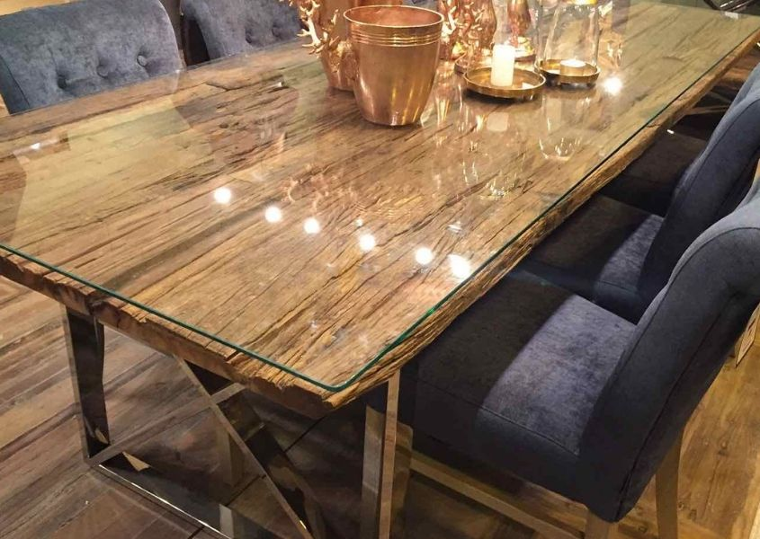 Close up of rustic reclaimed wood dining table with glass top and blue fabric dining chairs