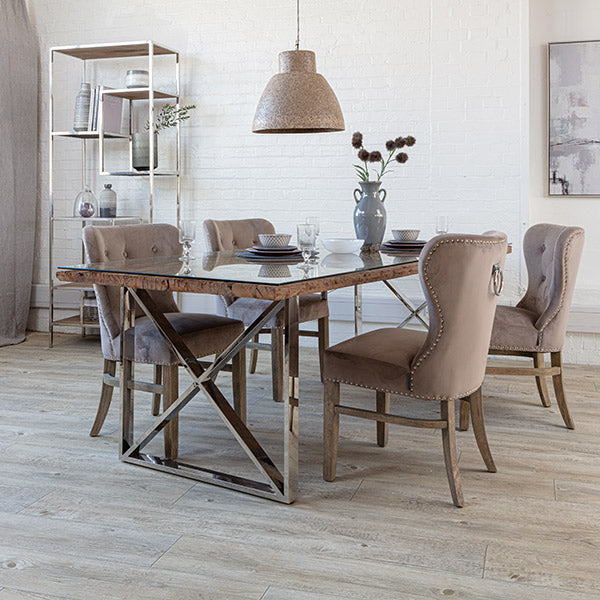Reclaimed wooden dining table with a glass tabletop and cream velvet dining chairs