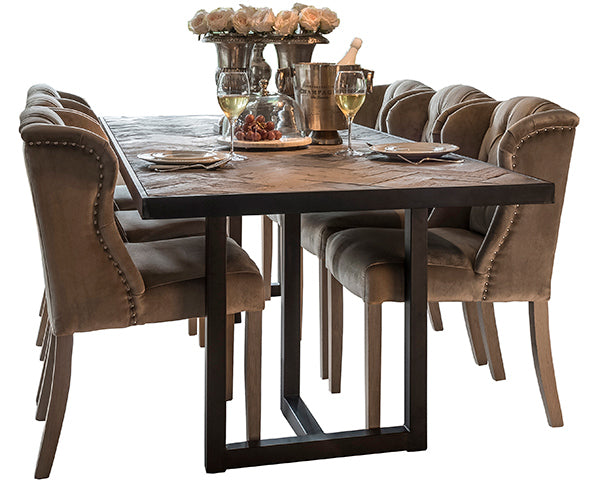 A reclaimed oak extending dining table with black steel legs and velvet dining chairs