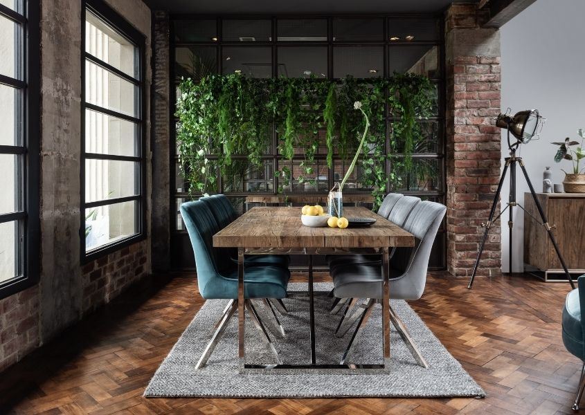 Industrial dining table with shiny steel legs and velvet dining chairs in dining room with hanging green plants