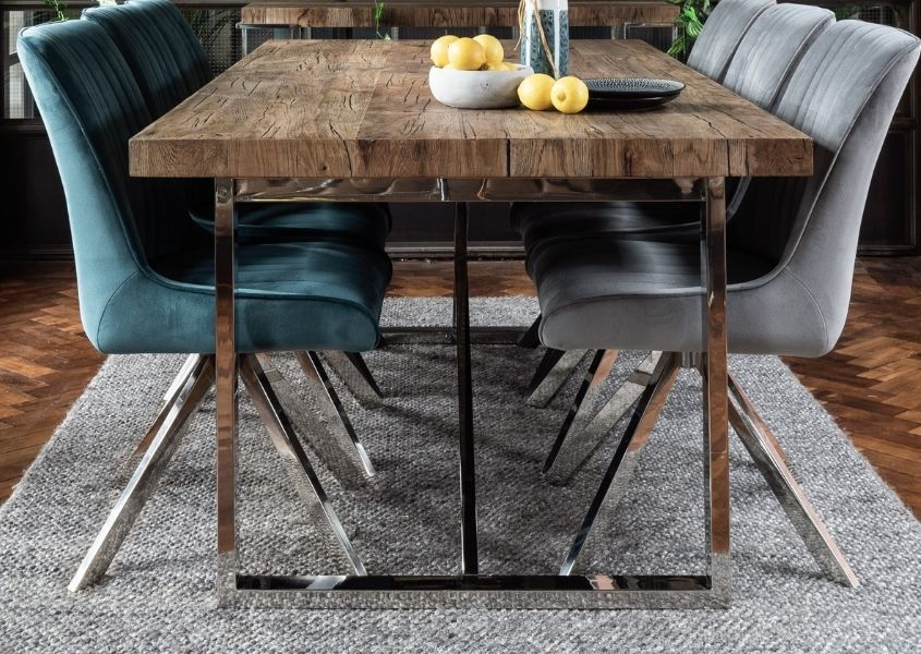 Rustic dining table with polished silver legs and velvet dining chairs