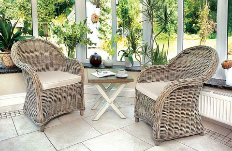 A pair of Grey Wash Rattan Armchairs with Cream Cushion in conservatory room