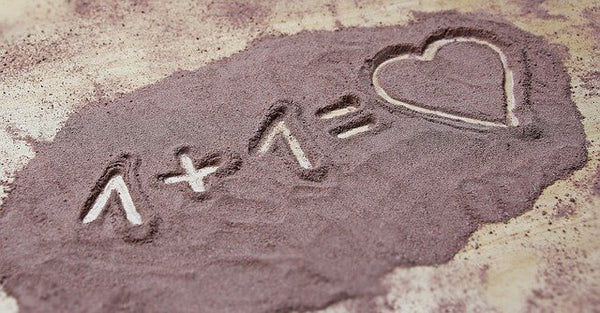 One plus one equals heart written in the sand