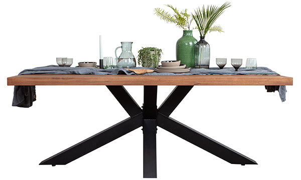 Industrial style dining table with a black steel spider leg, linen and ceramics on top
