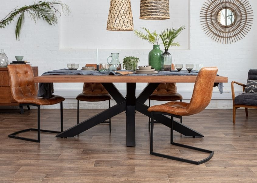 Rustic dining table with black steel spider legs, tan leather dining chairs and bamboo mirror on wall