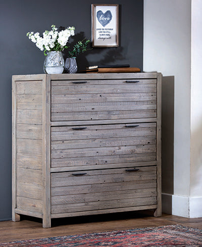 A reclaimed wood chest of drawers in a bedroom with a vase of flowers and a picture on top