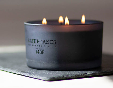 A Rathbornes scented candle in a black jar