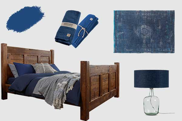A reclaimed wooden bed with blue bedding, a blue recycled glass lamp, a blue rug and blue linen