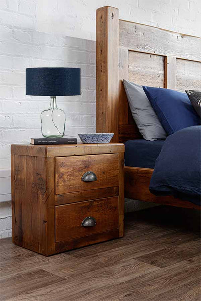 A blue recycled glass lamp on top of a rustic wooden bedside table in a bedroom