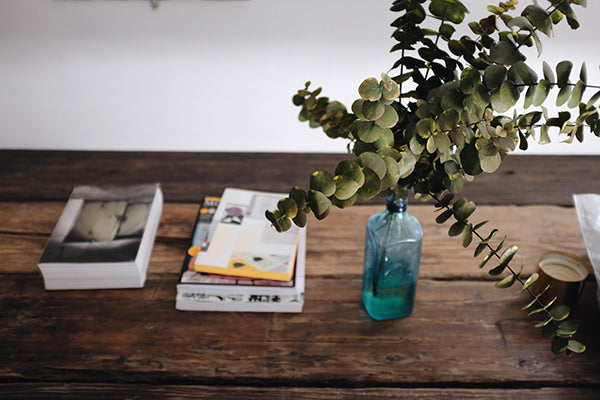 Books and a vase with eucalyptus on top of a rustic wooden surface