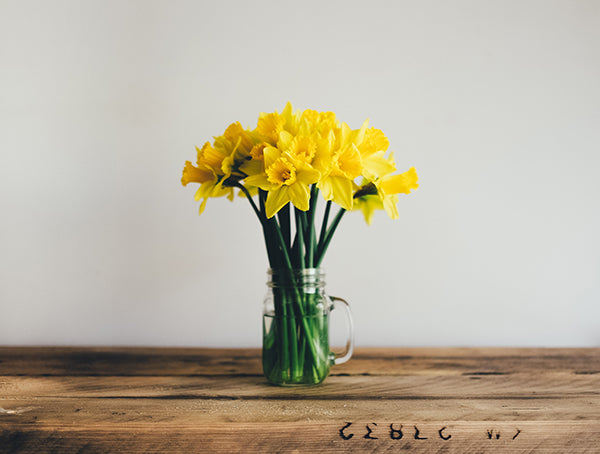 A bouquet of yellow flowers in a mason jar on top of a rustic wooden surface