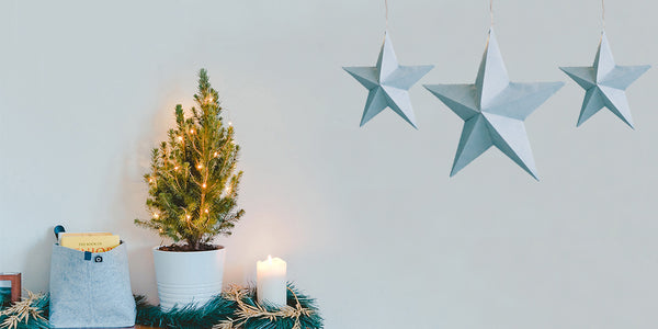 Small Christmas tree with fairy lights on a dark wooden mantelpiece with three hanging light blue stars