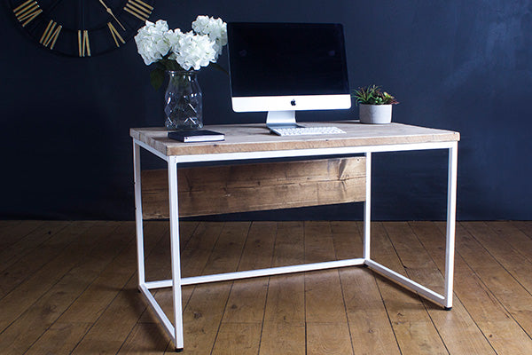 Reclaimed wood desk with white steel frame and decorative items on top
