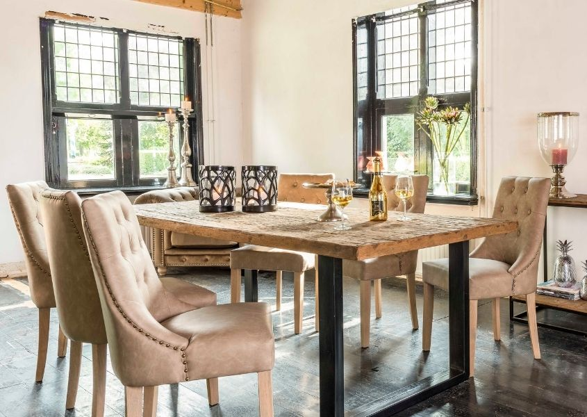 Industrial reclaimed wood dining table with fabric dining chairs and wine glasses on top
