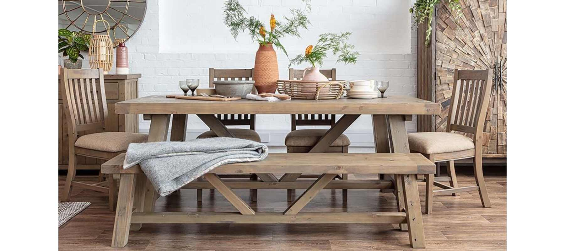 Wooden trestle table with wooden bench and terracotta vase