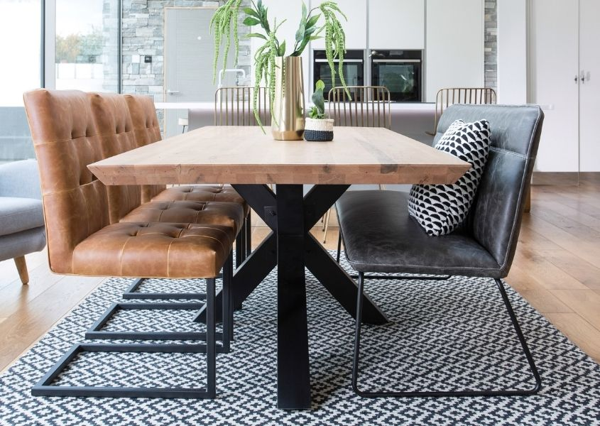 Industrial dining table with black steel spider leg, brown leather dining chairs and grey faux leather dining bench style with black and white rug