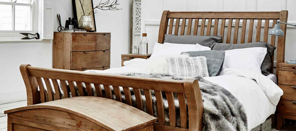 Reclaimed wood bed frame with grey faux fur throw
