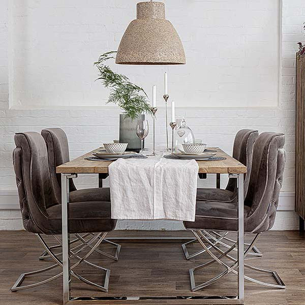 Rustic and glamorous dining table with velvet taupe chairs, a cream pendant and white table linen