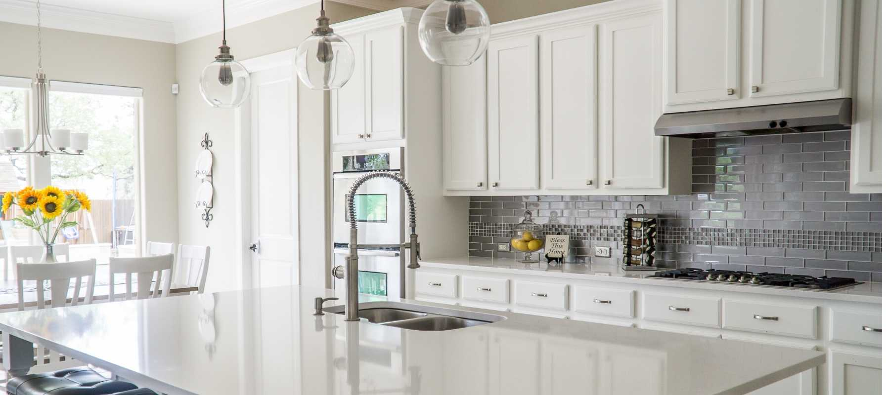 White kitchen with glass hanging pendants
