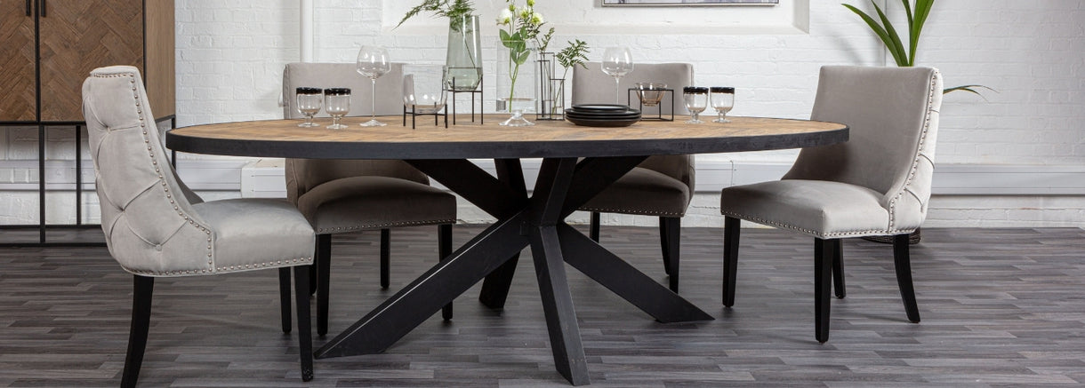 Lifestyle image of natural oak and black parquet oval dining table, surrounded by upholstered dining chairs.
