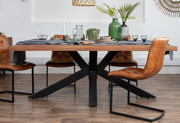 Industrial oak dining table with black steel spider legs and industrial dining chairs