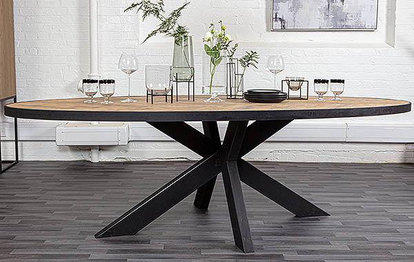 Oval oak dining table on steel legs with greenery and tableware on top