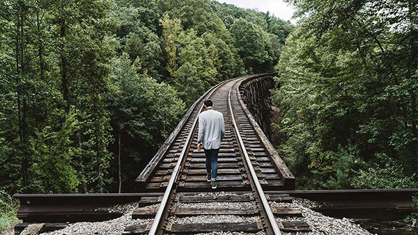 Man walking on wooden railway in the middle of the forest