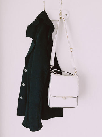 Black coat hanging on hook with white bag