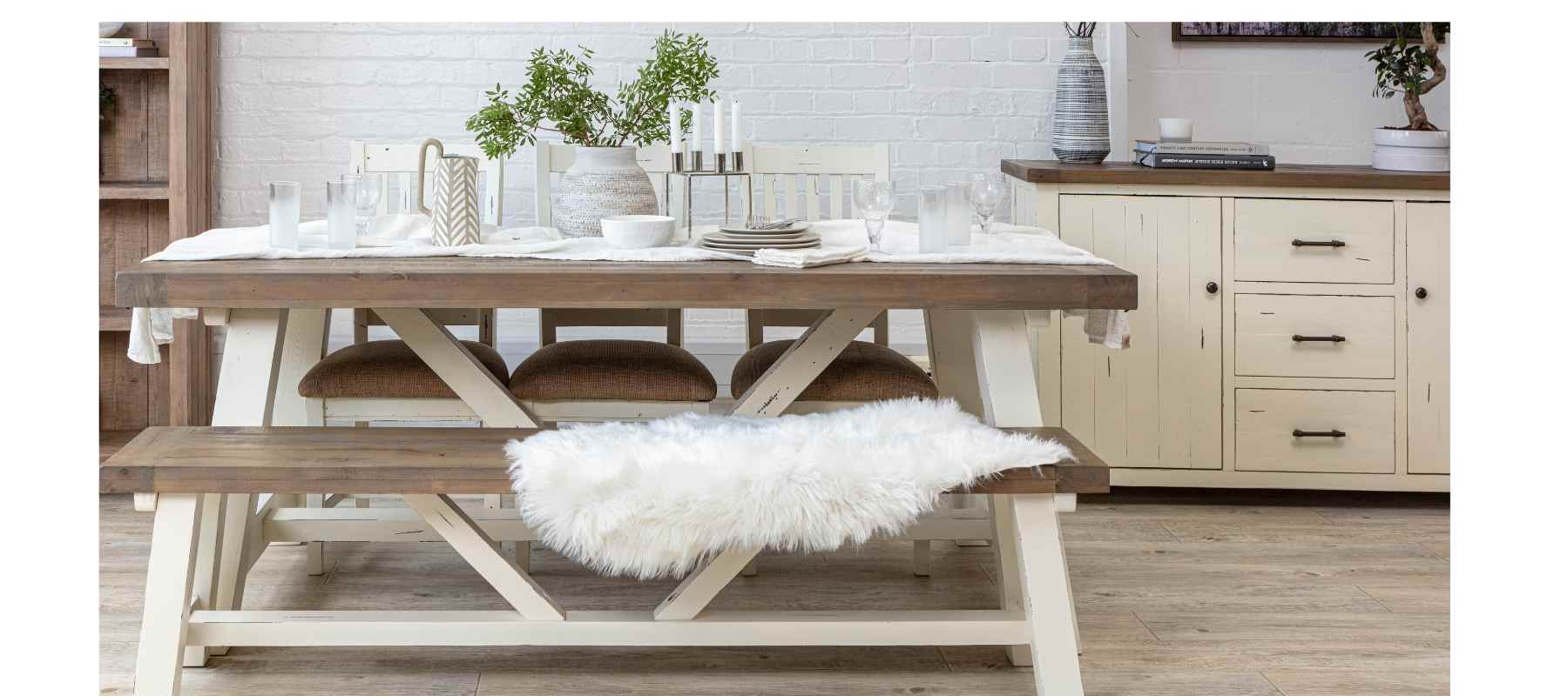 Farmhouse style wooden table with white legs and matching wooden dining bench