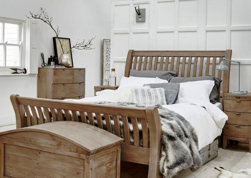 White bedroom with reclaimed wood bed, blanket box and side tables with grey faux fur throw on bed
