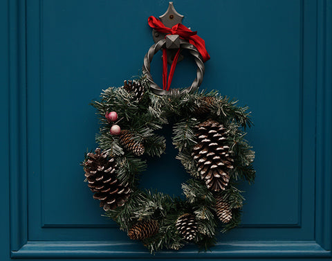 A Christmas wreath on a dark blue front door