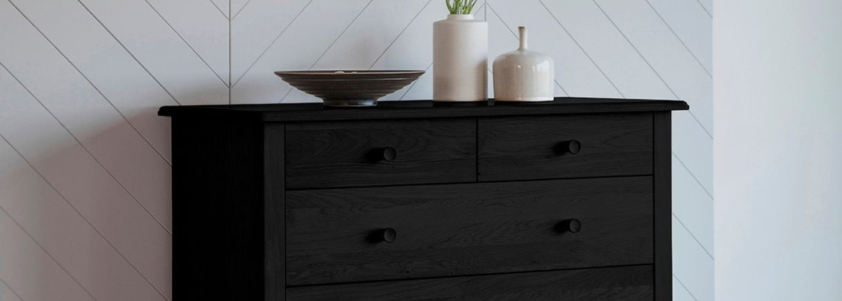 The striking Wycombe Black Oak 5 Drawer Chest stands against a white wall