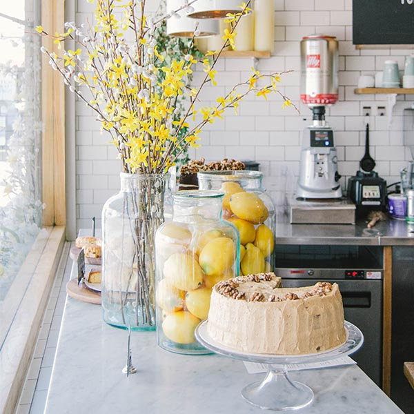 Yellow Flowers on Table with Lemons and Cake