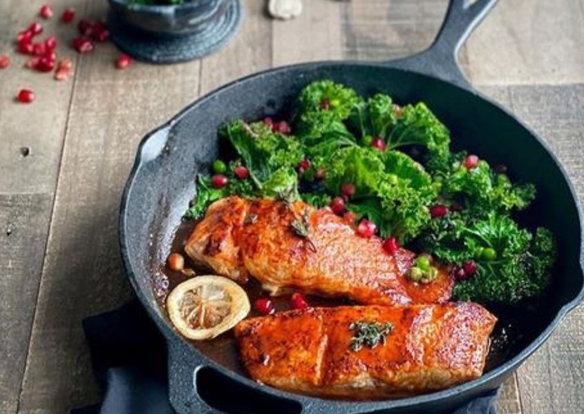 Black pan with cooked salmon and kale on reclaimed wood dining table