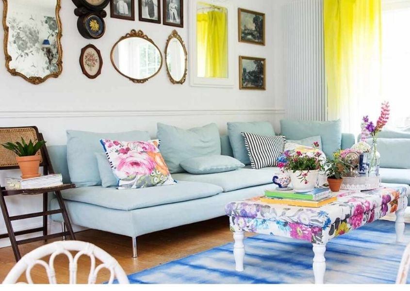 Pale blue sofa with white coffee table and display of mirrors on the wall