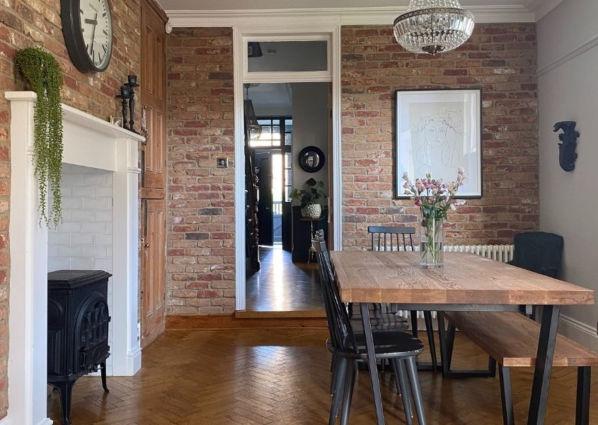 Industrial dining table next to white fireplace and woodburner with exposed brick walls