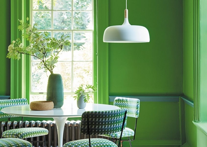 Dining room with bright green walls, large window, white round dining table and white hanging pendant light