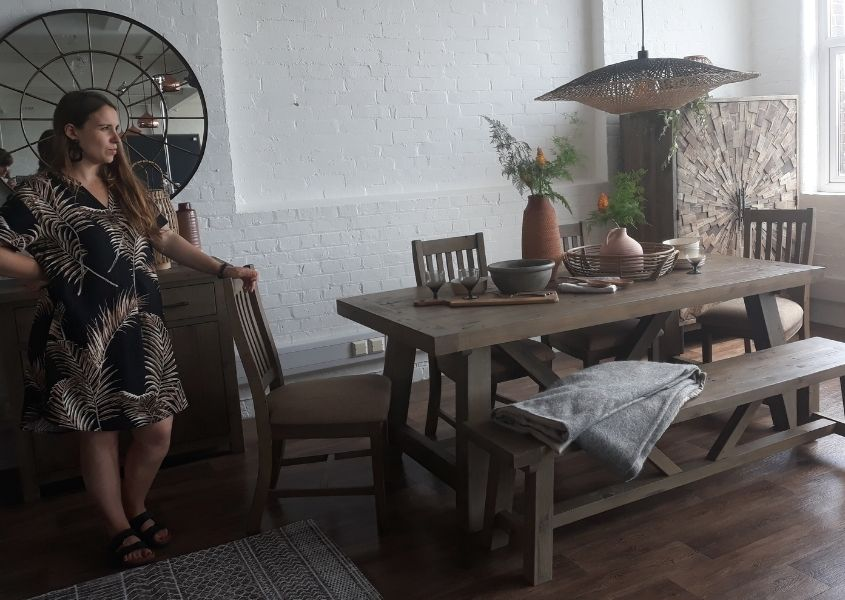 Women standing at a photo shoot of a reclaimed wood dining table and bench