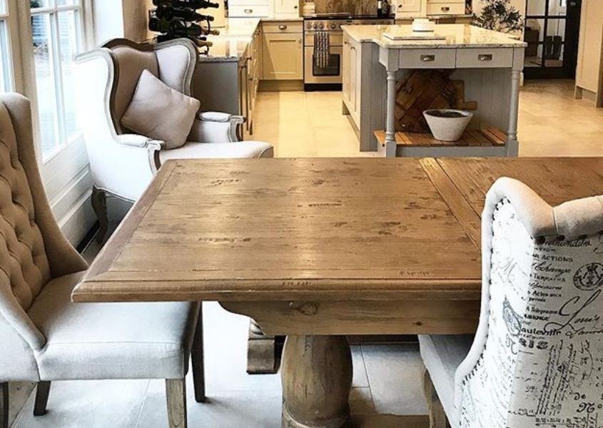 Close up of rustic dining table with cream fabric dining chairs and kitchen in background