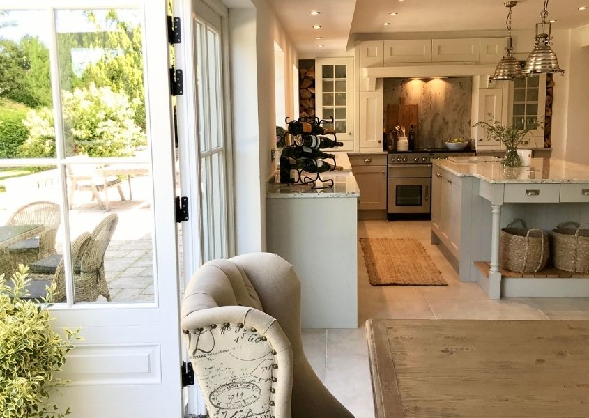 View of grey wooden kitchen with white french doors open to garden