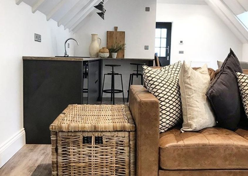 Brown leather sofa with large basket side table and small blue kitchen in background