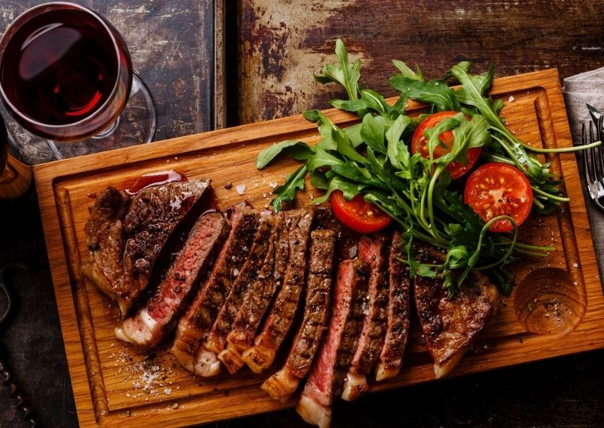 Slices of cooked steak on wooden board with green salad and glass of red wine