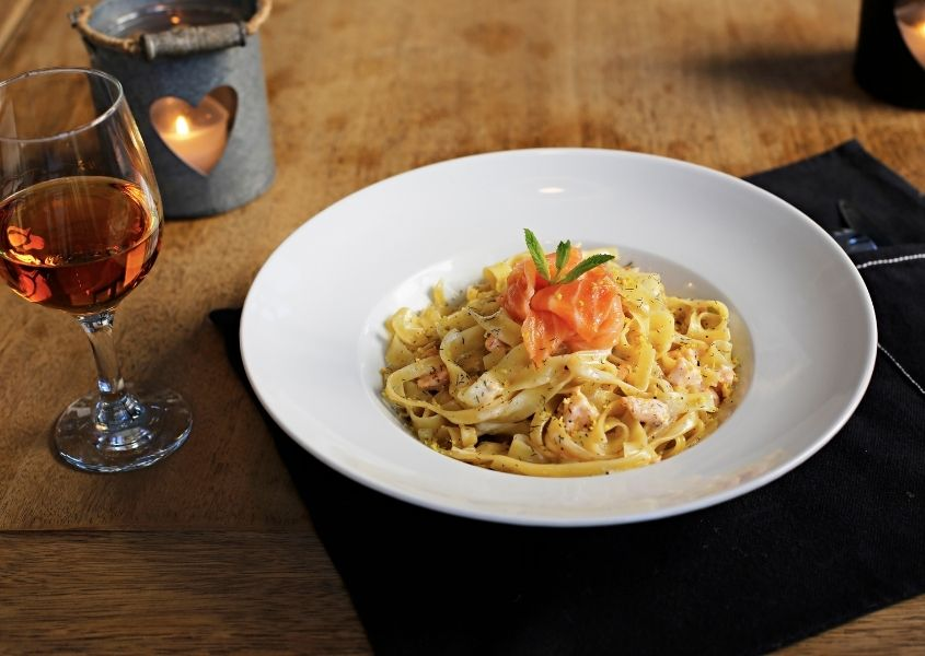 White bowl of salmon pasta on wooden dining table with black fabric plate mat and glass of wine