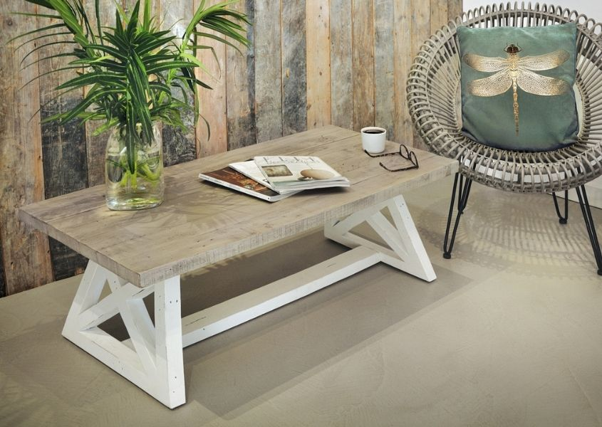 Reclaimed wood coffee table with white trestle legs and round rattan armchair in corner