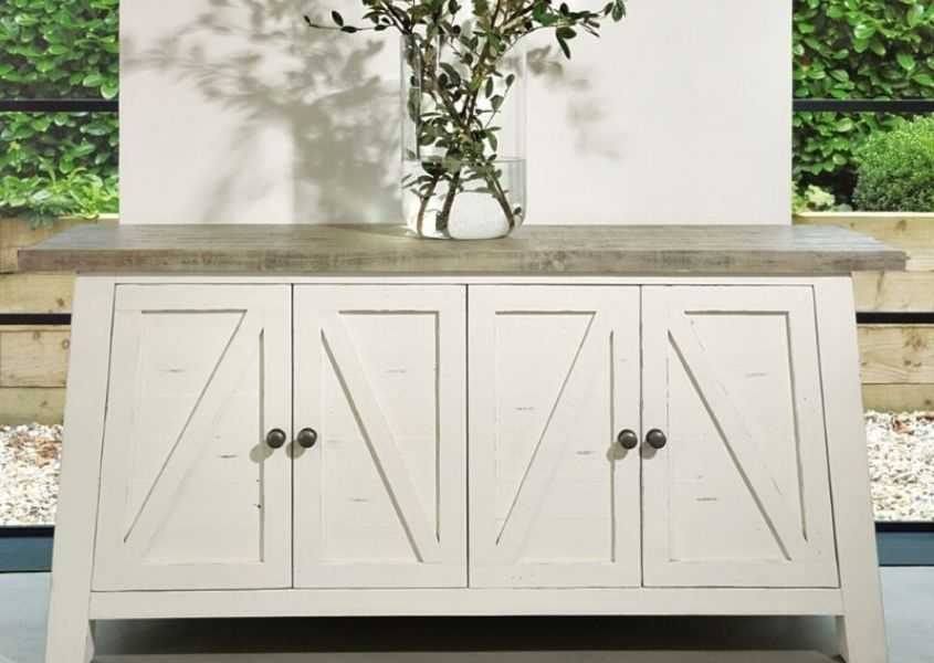 White reclaimed wood sideboard with tall glass vase and green stems