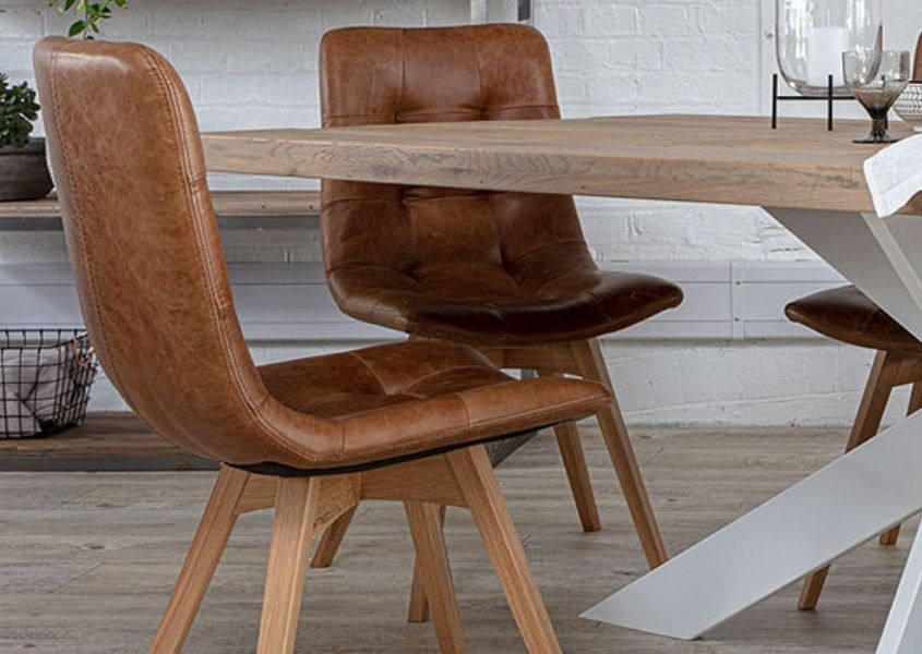 Brown leather dining chairs with oak legs next to wooden table with white spider legs