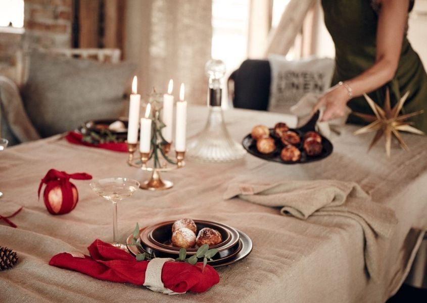 Woman laying Christmas dining table with beige table cloth, red linen napkins and gold star