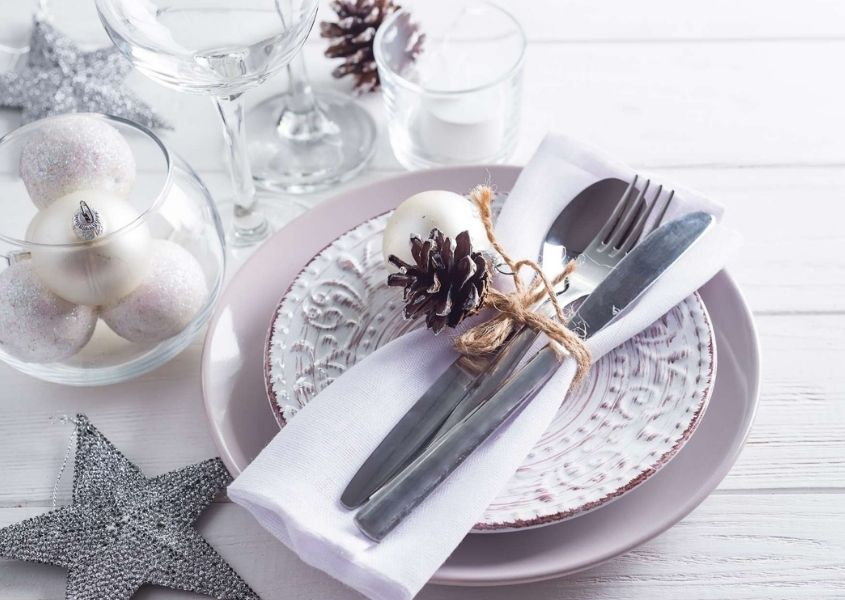 White and silver Christmas dining table decorations on white rustic dining table