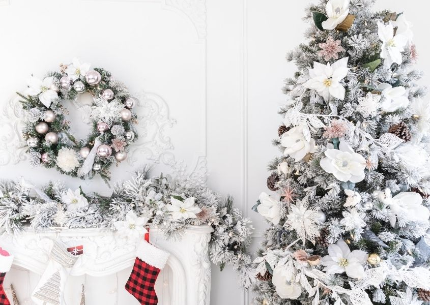 Christmas tree and white mantelpiece decorated in white and pastel decorations.
