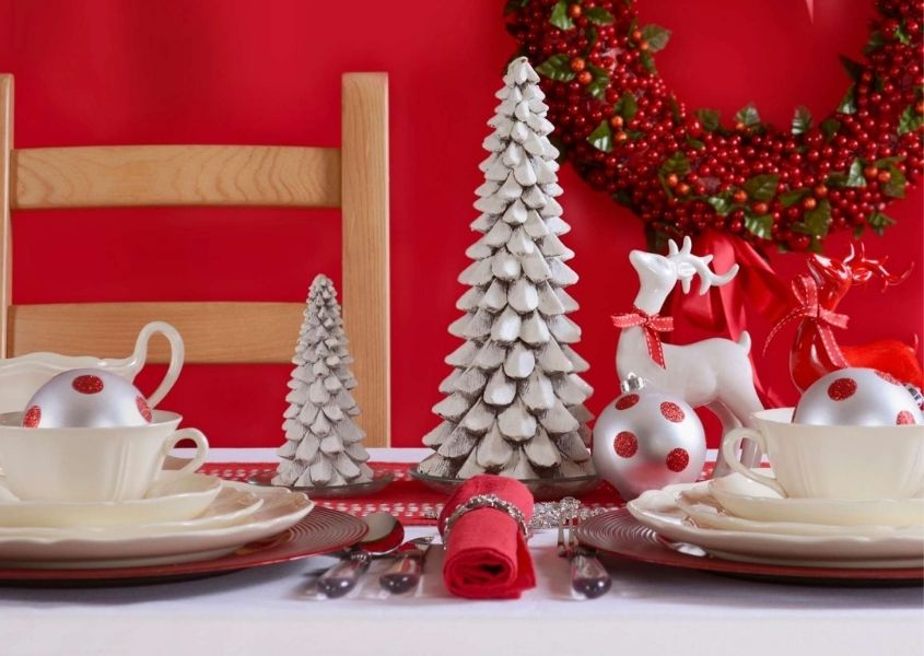 Christmas dining table with red background and white christmas tree decorations